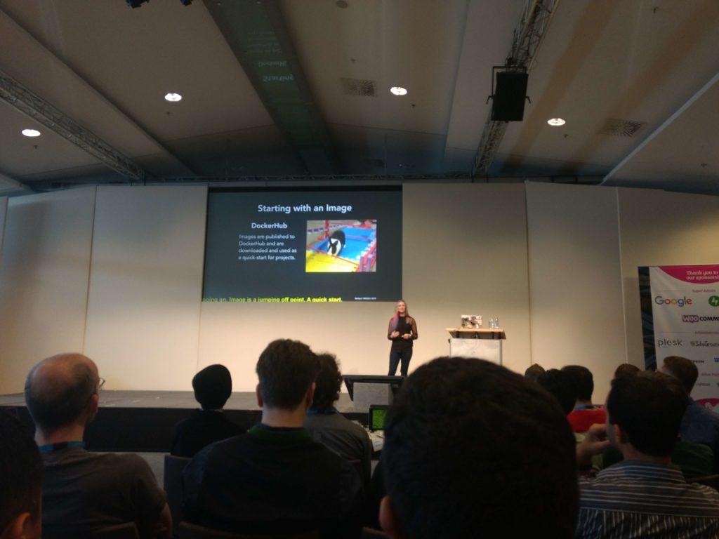 Maura vertelt op het podium over ontwikkelen met Docker