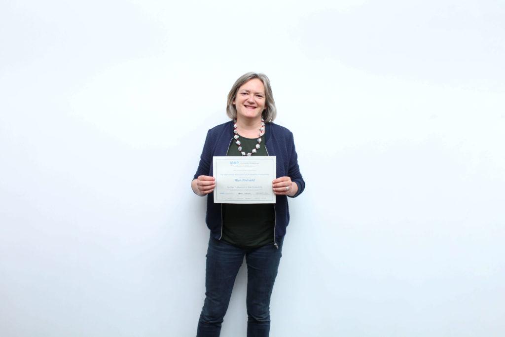 Rian houd haar IAAP Certificaat vast.