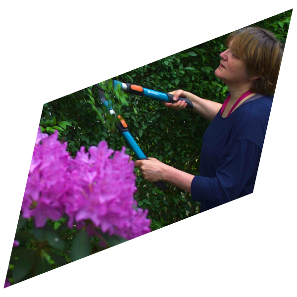 Rian Rietveld at work with a hedge trimmer in her garden