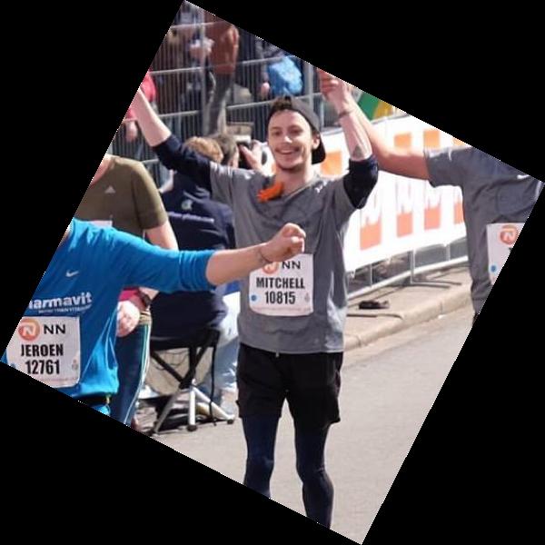 Photo of Mitchell passing the finish line of the Rotterdam Marathon